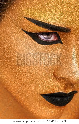 Golden Woman's Face Close up. Futuristic Gilded Make-up. Painted Skin