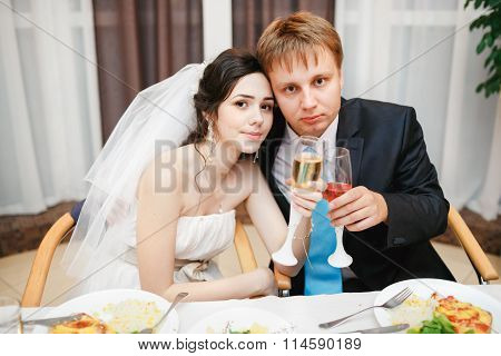 Newlyweds at the wedding table sitting together, posing with wine. Attractive beautiful bride, kind