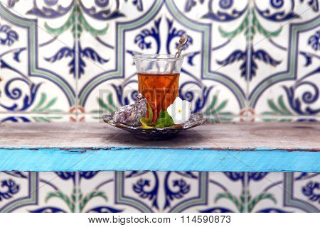 Vintage Arabic  glass full of tea on metal saucers near the white flower s and fig