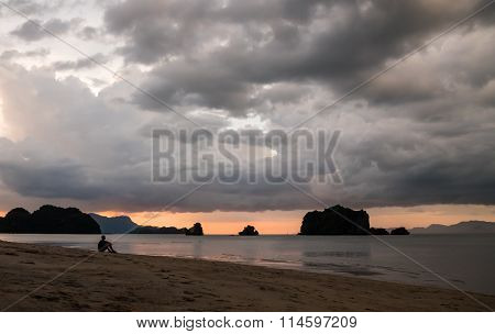 Man Sitting on Beach After Sunset