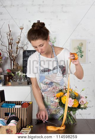Adult Florisr Girl Cutting A Ribbon For Bouquet