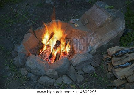 The fire in the stone hearth.