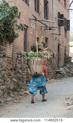 Nepali Woman In National Clothes With Baskets On Walk In Old Town
