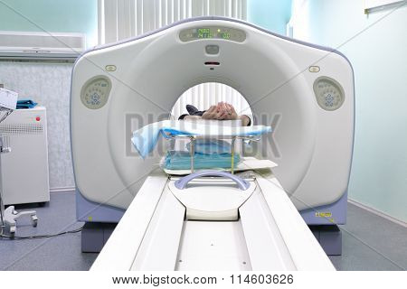 Patient being scanned and diagnosed on CT (computed tomography) scanner in hospital.