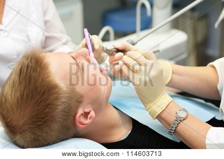 Young male patient makes professional dental treatment in dental office