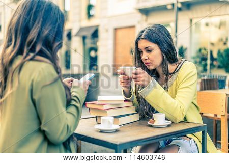 Women With Smartphones In A Bar