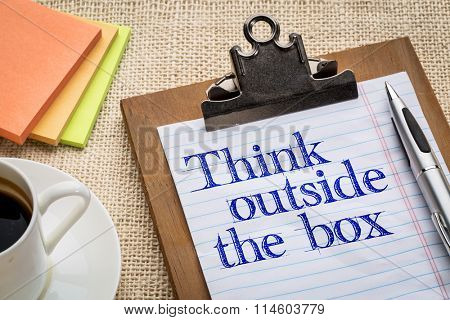 think outside the box - motivational slogan on a clipboard with a cup of coffee