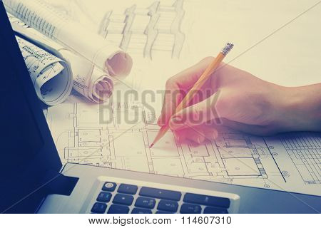 Architect working on blueprint. Architects workplace - architectural project, blueprints, ruler, cal