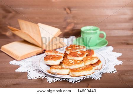 Plate With Ruddy Pancakes Against The Opened Book And A Green Cup