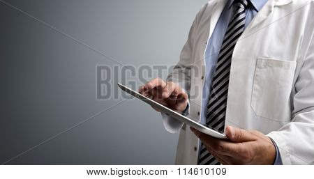 Doctor using digital tablet on gray background