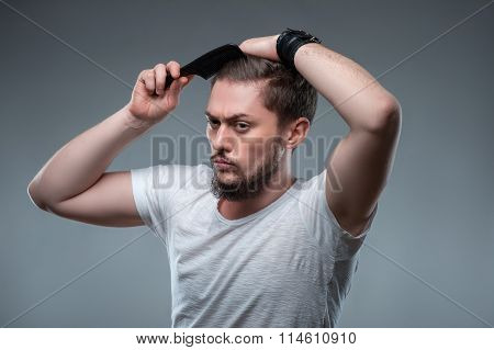 Attractive bearded young guy is making hairstyle