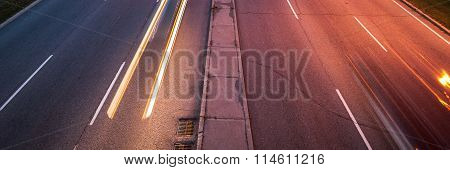 Traffic in the night.  Light streaks from passing cars illuminate the pavement.