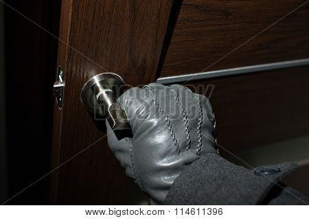 Man's Hand In A Black Glove Opening The Door