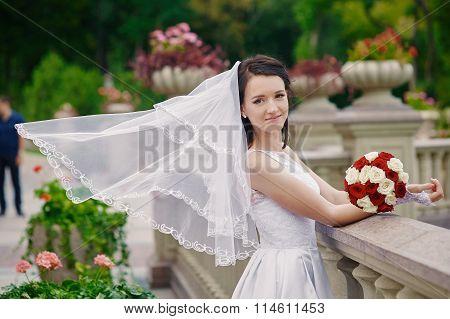 Emotional Brunette Bride In White Dress Posing At Balcony Near Stone Railing