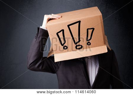 Businessman standing and gesturing with a cardboard box on his head with exclamation point