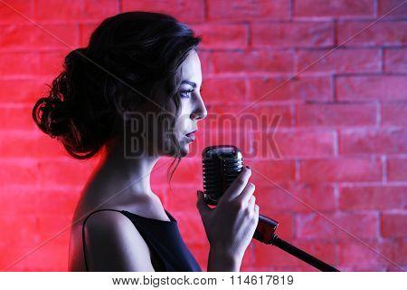 Beautiful brunette singing woman  on brick wall background