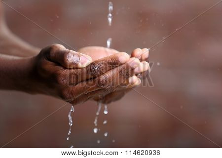 Hands washing concept. Water pouring into man hands on brick wall background