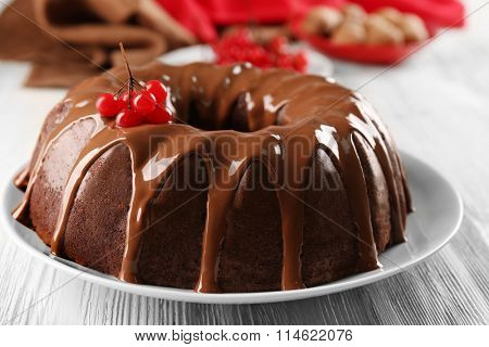 Chocolate cake with snow ball tree berries on plate on a table