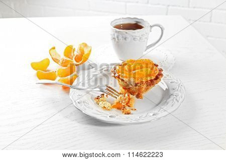 Sweet cake with tangerines on table, close up