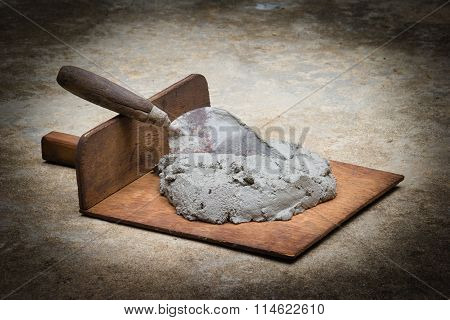 Brown construction trowel and mortar on ground