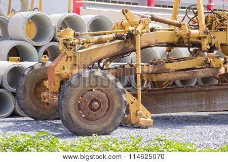 Close up yellow road grader, bulldozer and pipes