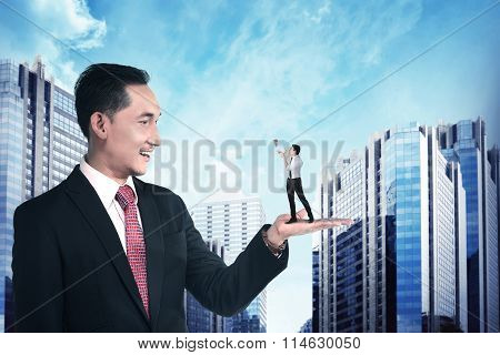 Giant Businessman Holding Little Man Yelling With Megaphone