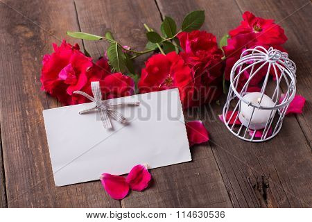 Empty Tag And Fresh Red Roses  On Aged Wooden Background.