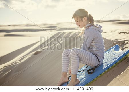 Little Girl Playing and Boarding in the Sand Dunes