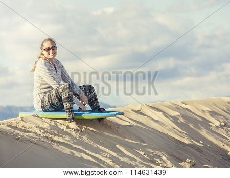 Woman Playing and boarding in the Sand Dunes