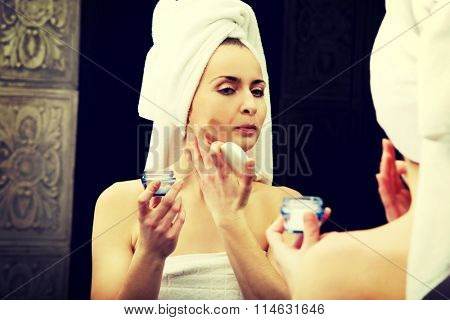Woman putting anti-aging cream on her face.