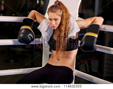 Girl wearing sport gloves sitting in corner of boxing ring.