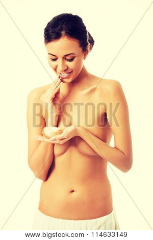 Topless woman with cream container