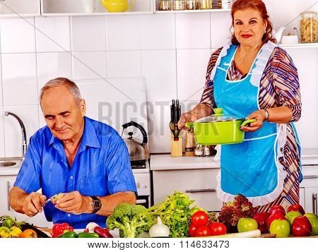 Senior couple cooking at kitchen.