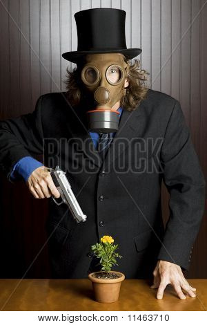 Man in gas mask holding gun with a flower