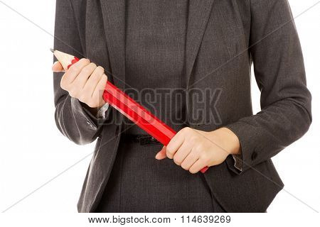 Woman holding oversized pencil.