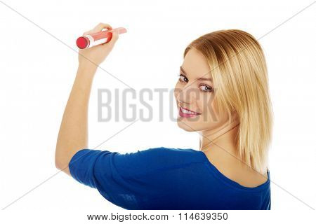 Woman writing with oversized pencil.