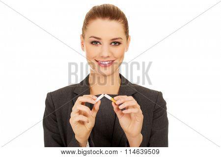 Business woman breaking cigarette.