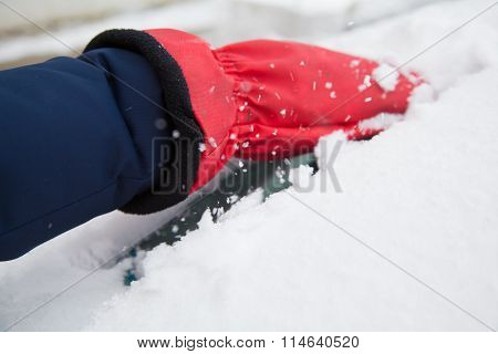 Woman Removing Snow From Car Window