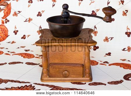 Old coffee grinder isolated on tablecloth