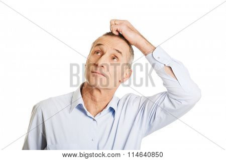 Portrait of confused man scratching his head