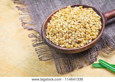 Golden flax seeds in wooden spoon