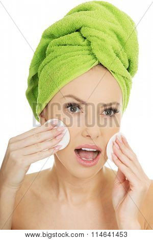 Shocked woman with cotton pads.