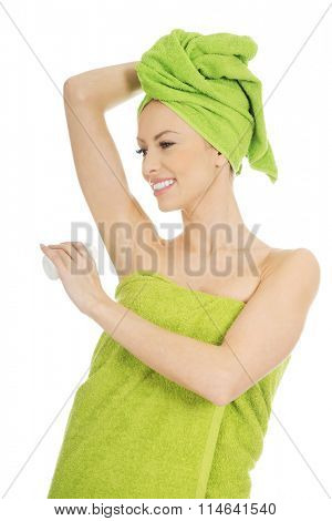 Young woman using deodorant.