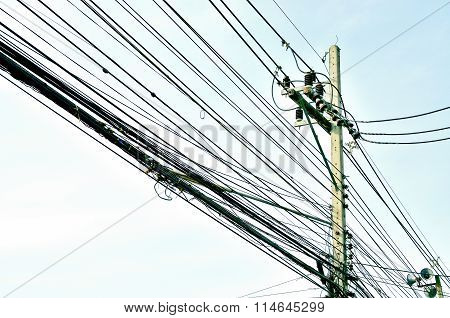 Tangle of electrical wires on blue sky background
