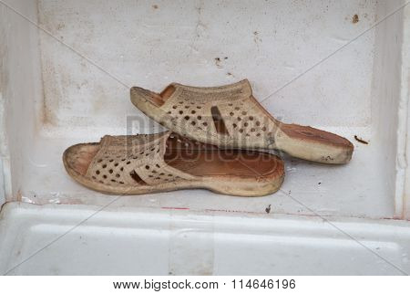 Close up of a pair of dirty sandal of a homeless man on a white box