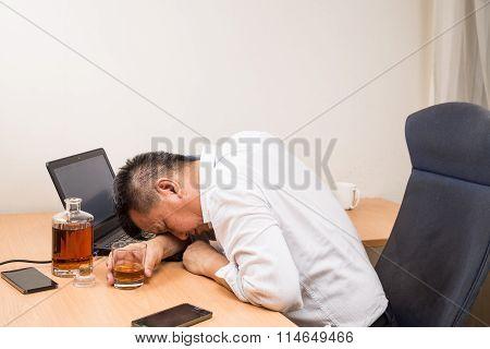Depressed Asian Business Manager Drunk On Office Desk
