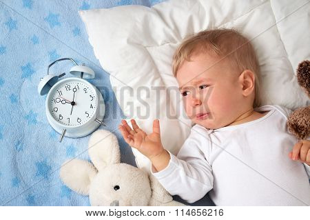 One year old baby with alarm clock