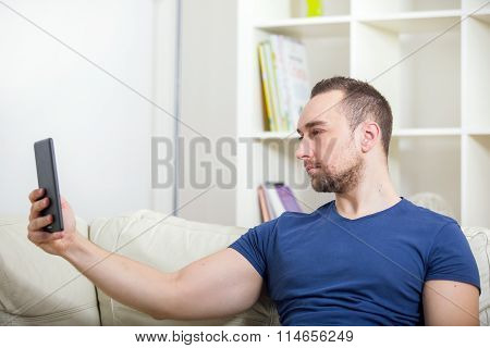 Young attractive 30s man taking selfie picture or self video with digital tablet at home