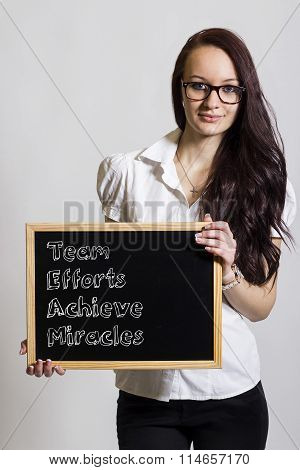 Team Efforts Achieve Miracles - Young Businesswoman Holding Chalkboard
