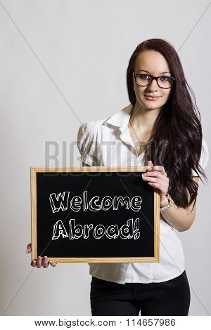 Welcome Abroad! - Young Businesswoman Holding Chalkboard